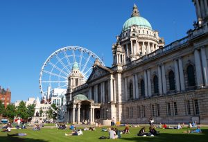 Belfast city hall and people sitting outside on the lawn in the sun